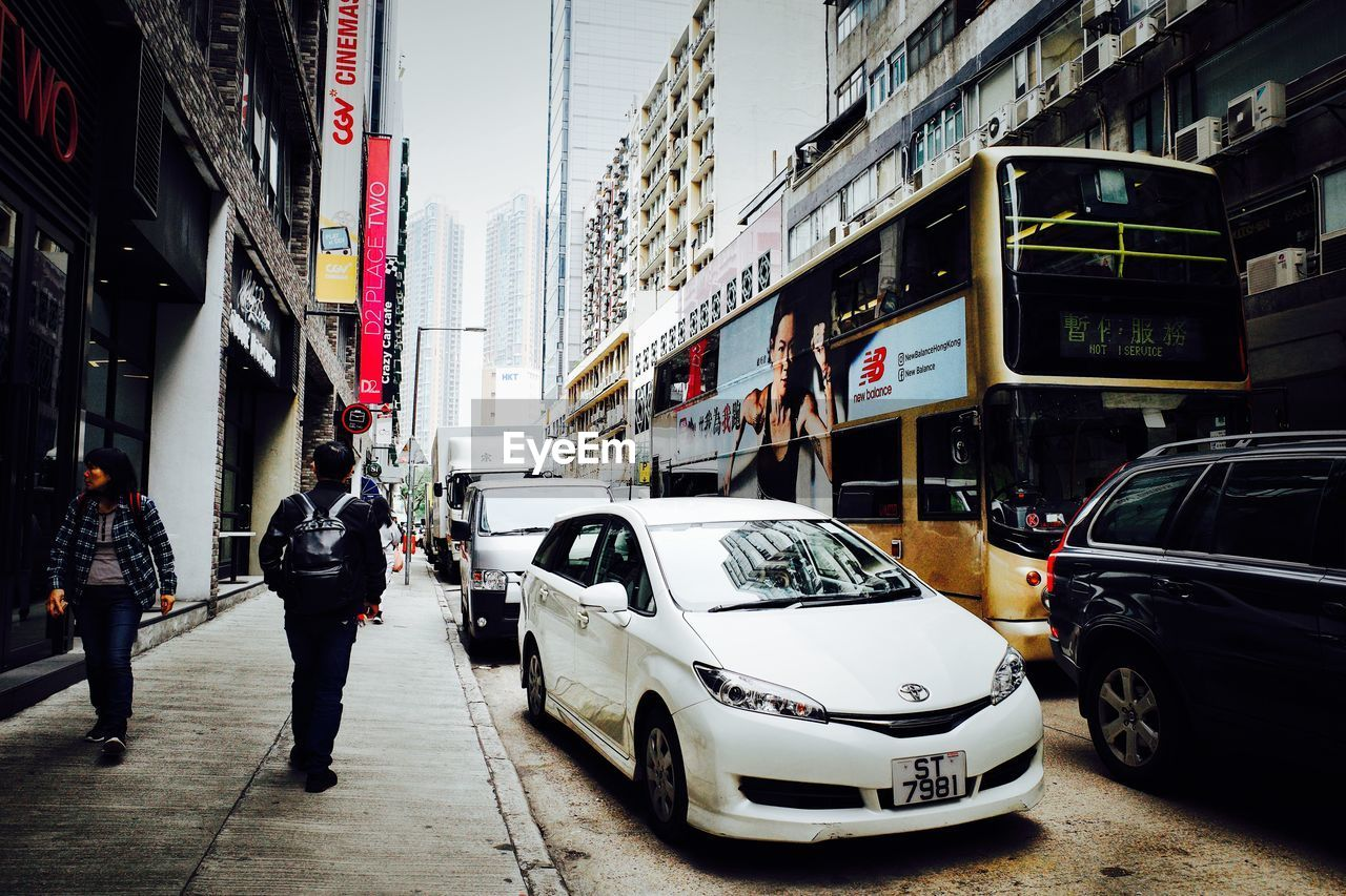 car, motor vehicle, mode of transportation, city, transportation, building exterior, land vehicle, architecture, built structure, real people, street, building, road, city life, incidental people, day, people, city street, men, full length