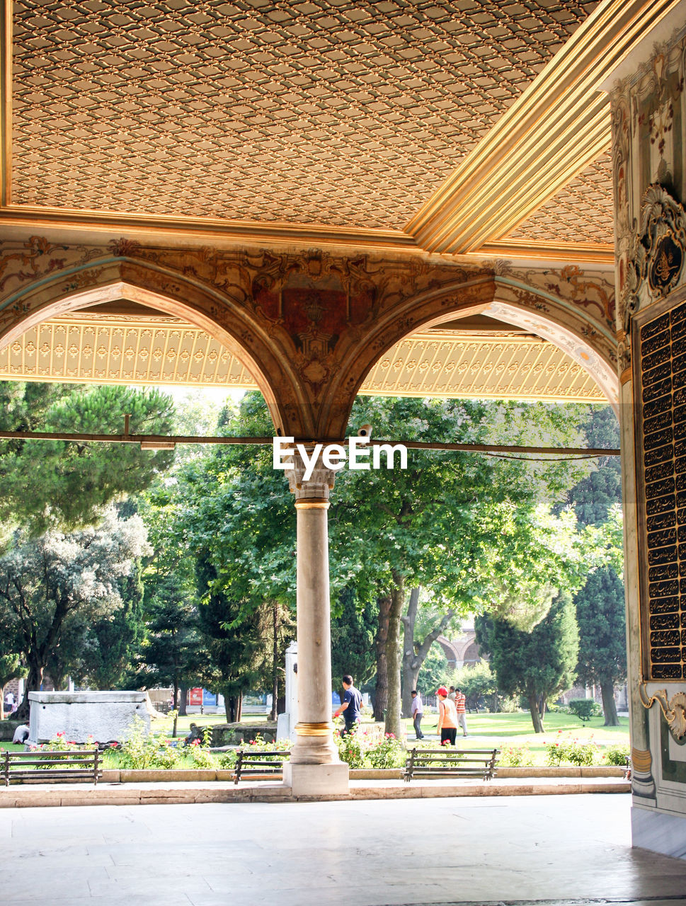 architecture, built structure, arch, architectural column, plant, incidental people, tree, building exterior, day, nature, building, the past, history, travel destinations, outdoors, sunlight, travel, arcade, tourism, in a row, colonnade, courtyard