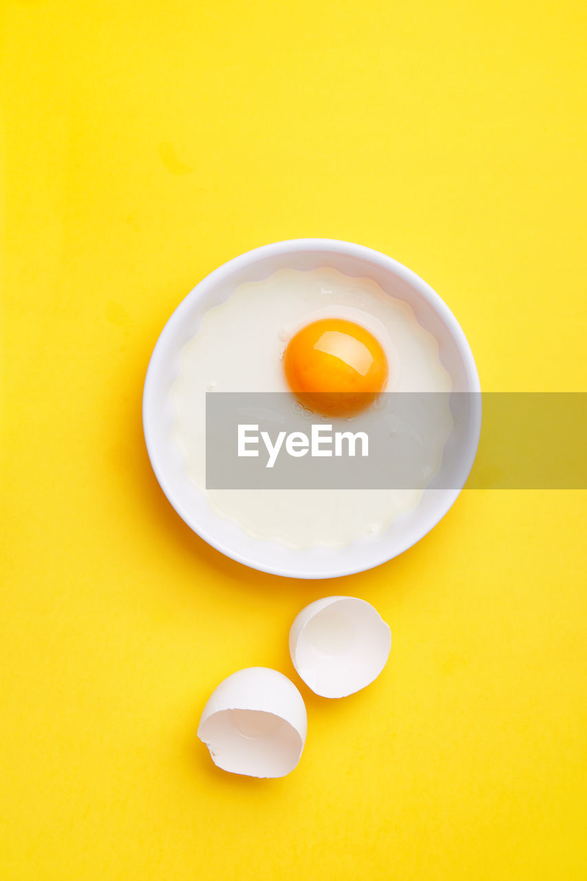 yellow, studio shot, still life, yellow background, indoors, egg yolk, food and drink, white color, no people, food, wellbeing, egg, directly above, colored background, freshness, medicine, healthcare and medicine, pill, high angle view, dose