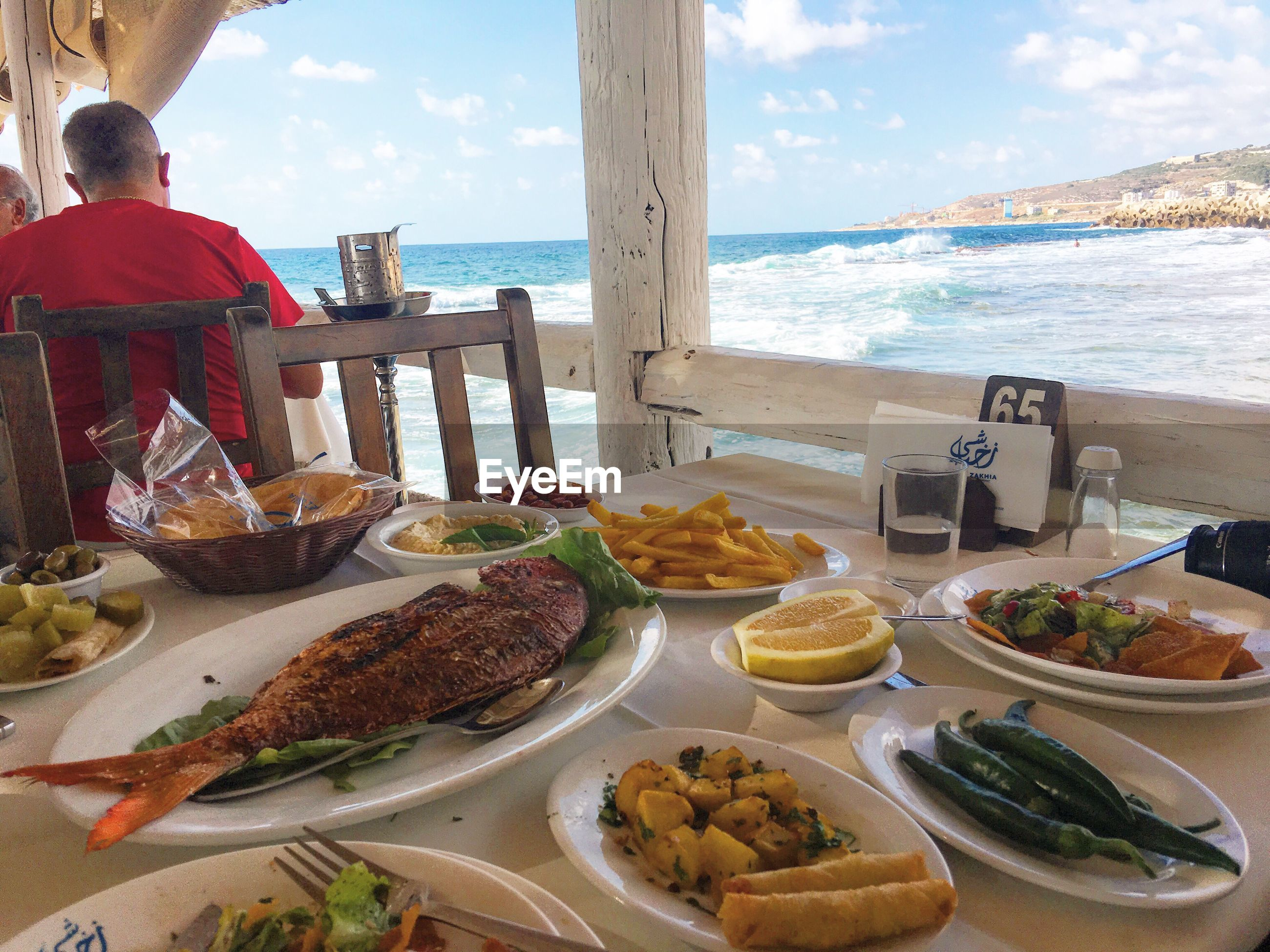 plate, food and drink, sea, food, table, serving size, water, healthy eating, day, ready-to-eat, real people, outdoors, sky, one person