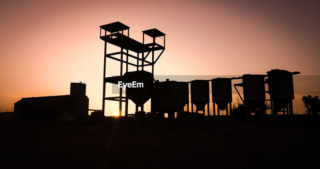 sunset, silhouette, sky, architecture, built structure, orange color, nature, copy space, clear sky, outdoors, no people, industry, building exterior, land, tower, sun, building, lifestyles