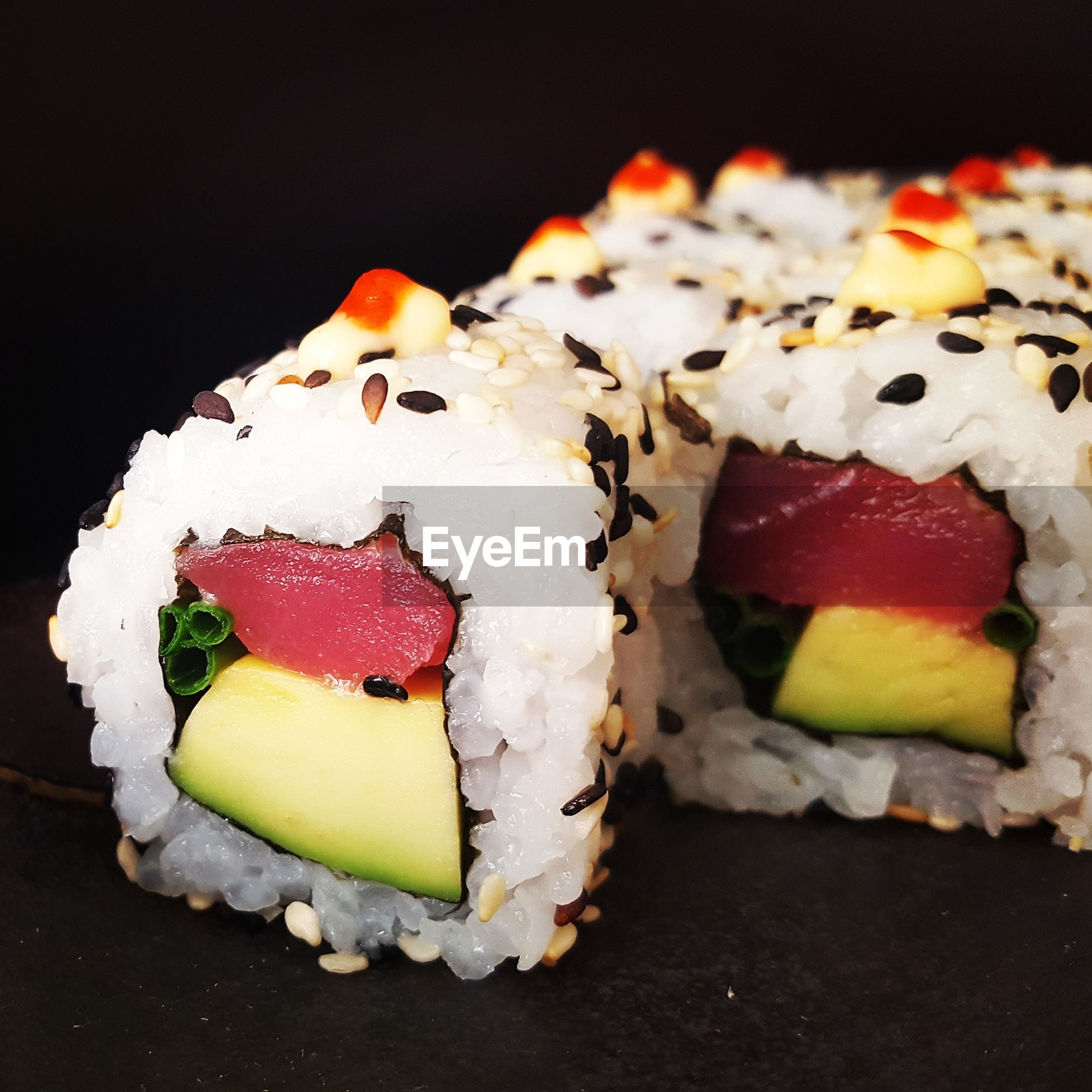 Close-up of sushi served against black background