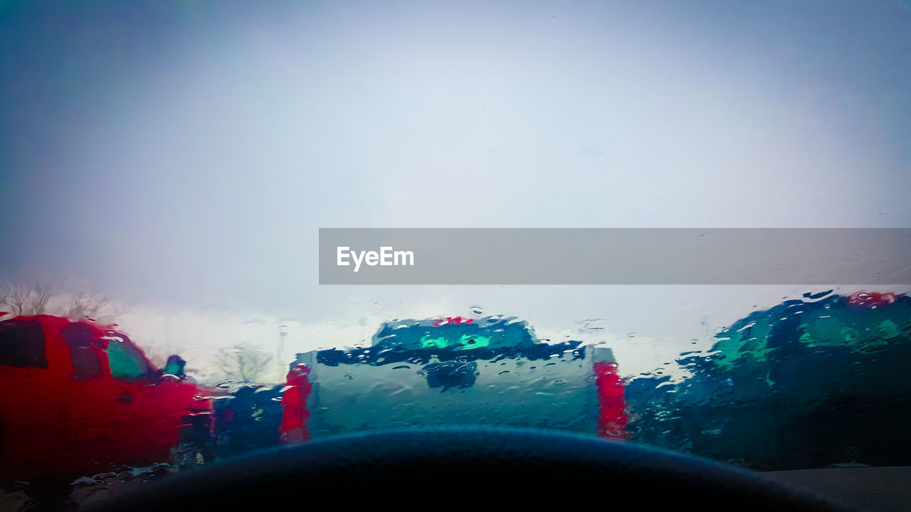 Cars Against Sky Seen From Wet Windshield