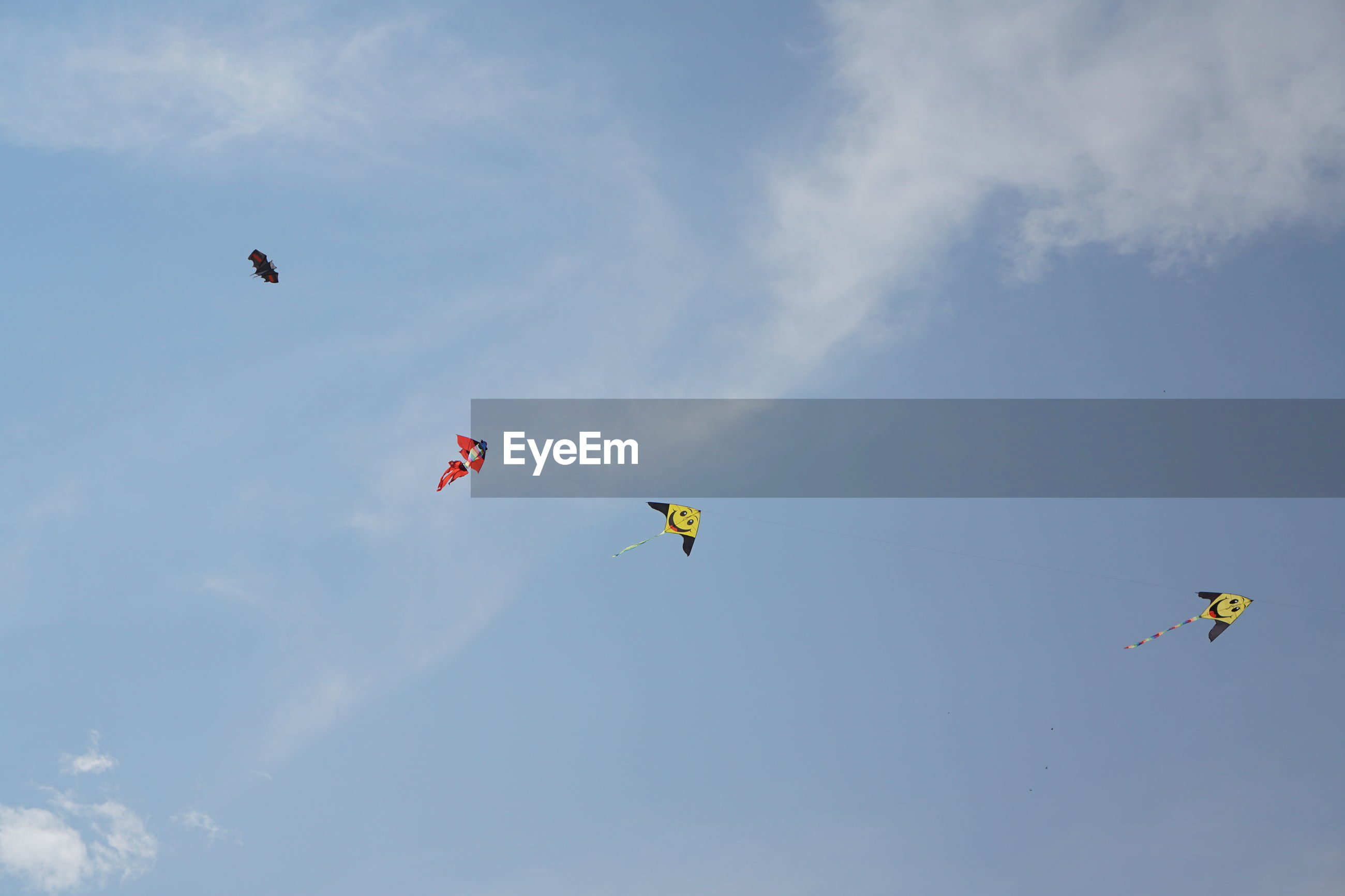 Low angle view of kites flying in sky