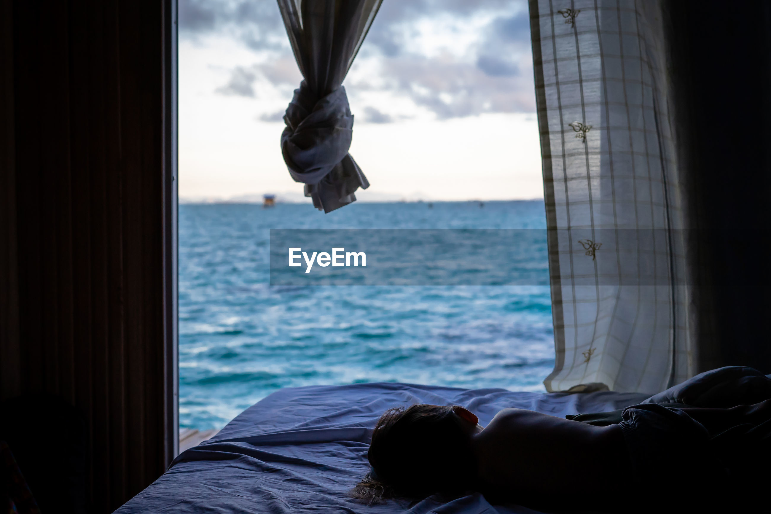 LOW SECTION OF MAN LYING BY SEA AGAINST SKY SEEN THROUGH WINDOW
