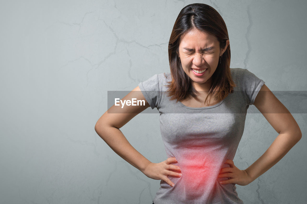 Young woman suffering from stomachache standing against wall