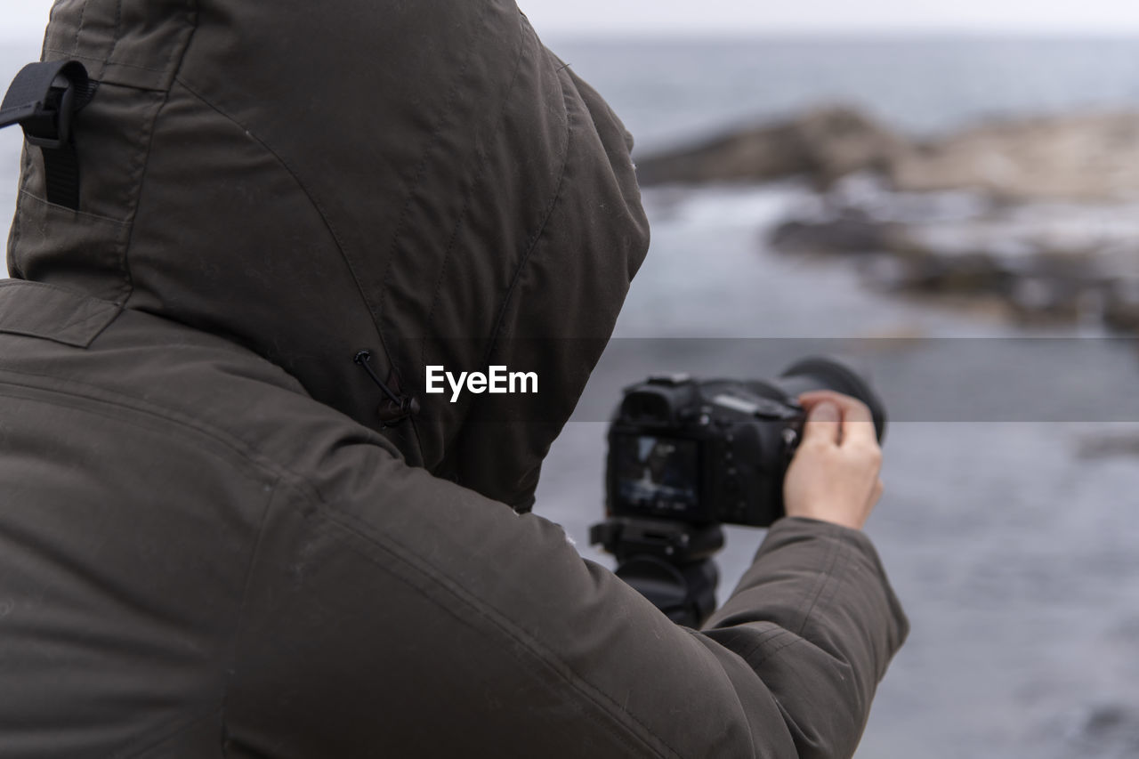 photography themes, photographing, activity, camera - photographic equipment, one person, photographic equipment, technology, real people, holding, camera, digital camera, lifestyles, men, occupation, leisure activity, focus on foreground, photographer, clothing, winter, warm clothing, digital single-lens reflex camera