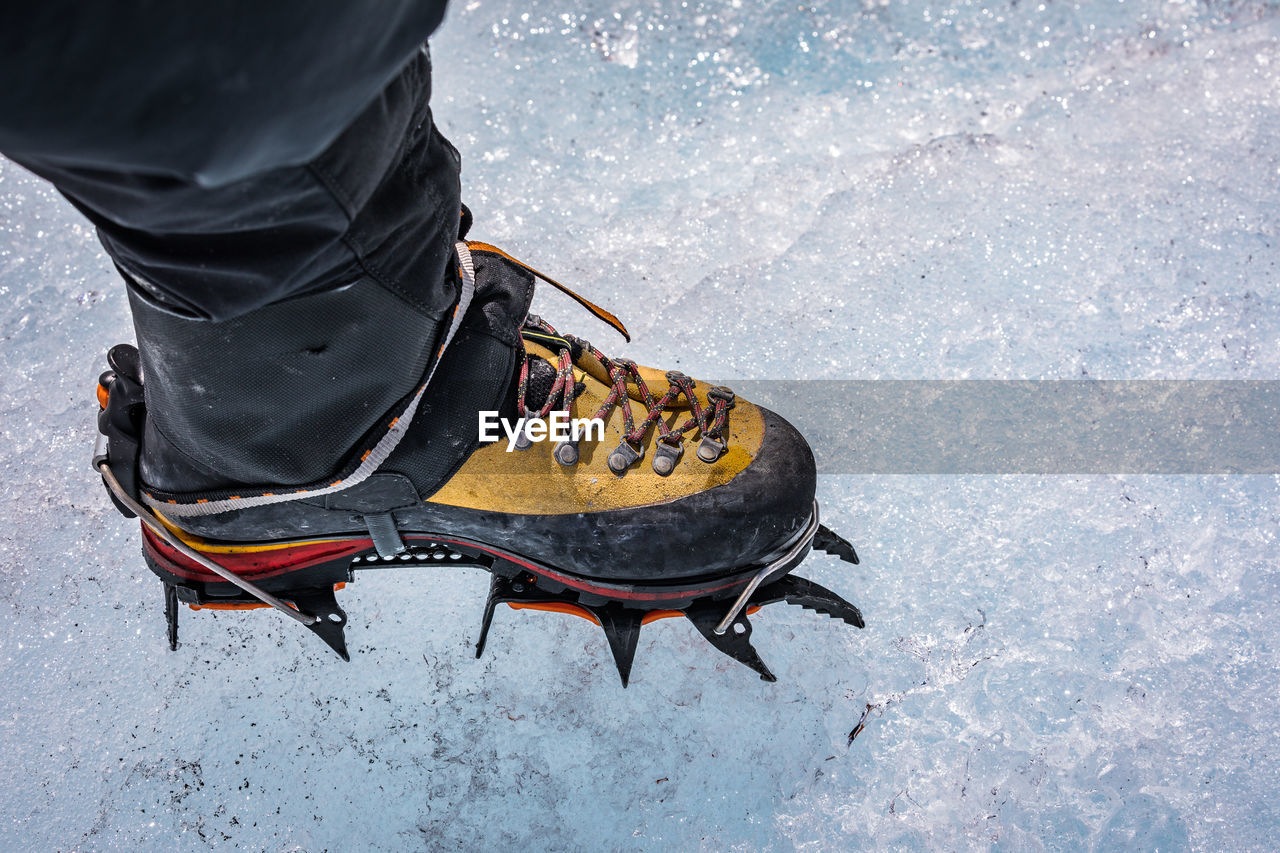 Low Section Of Hiker Wearing Crampon While Standing On Snow