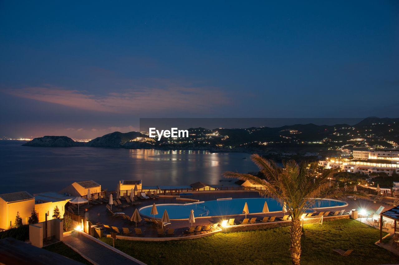 Illuminated Tourist Resort By Sea Against Sky At Dusk