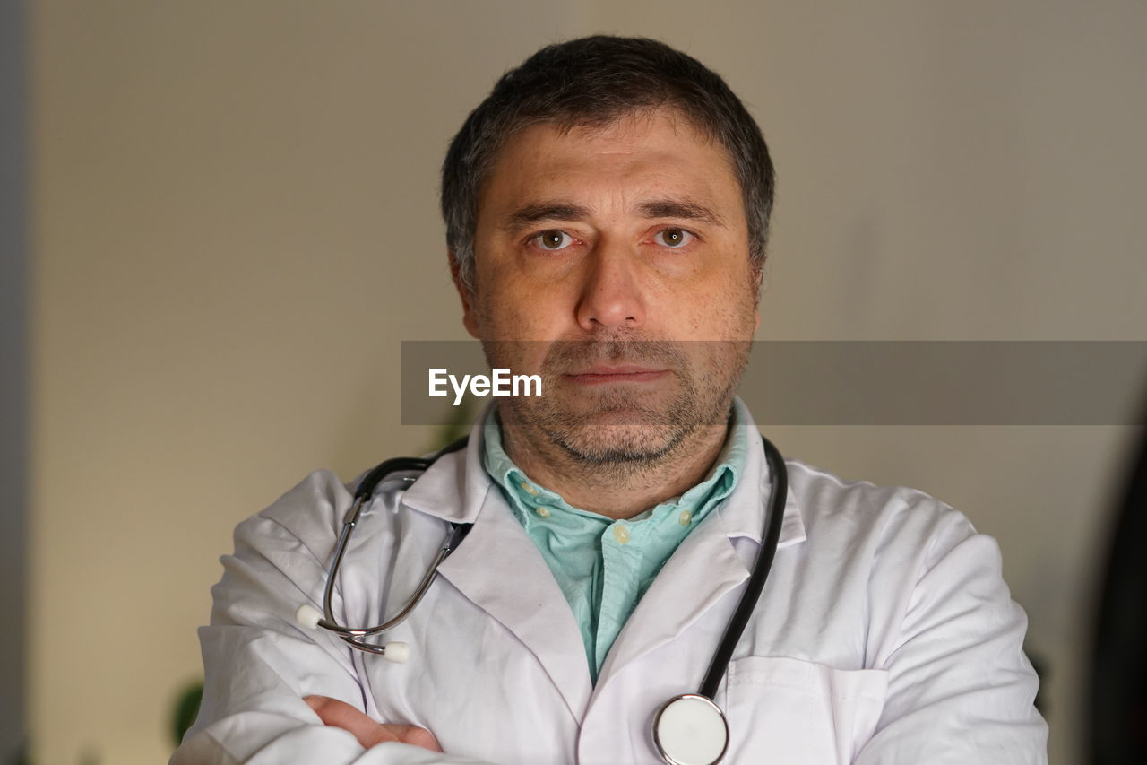 Portrait Of Mature Doctor Against Wall
