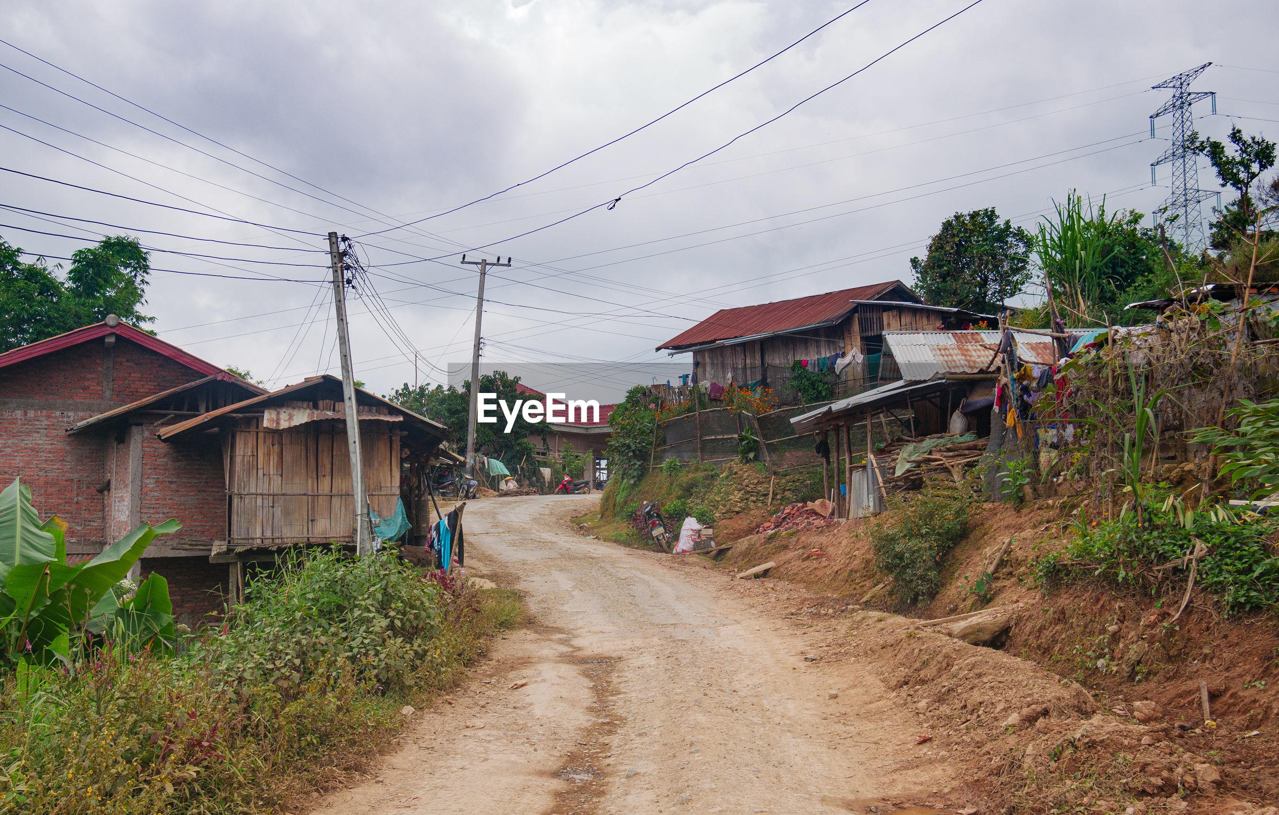 HOUSES BY DIRT ROAD AGAINST SKY