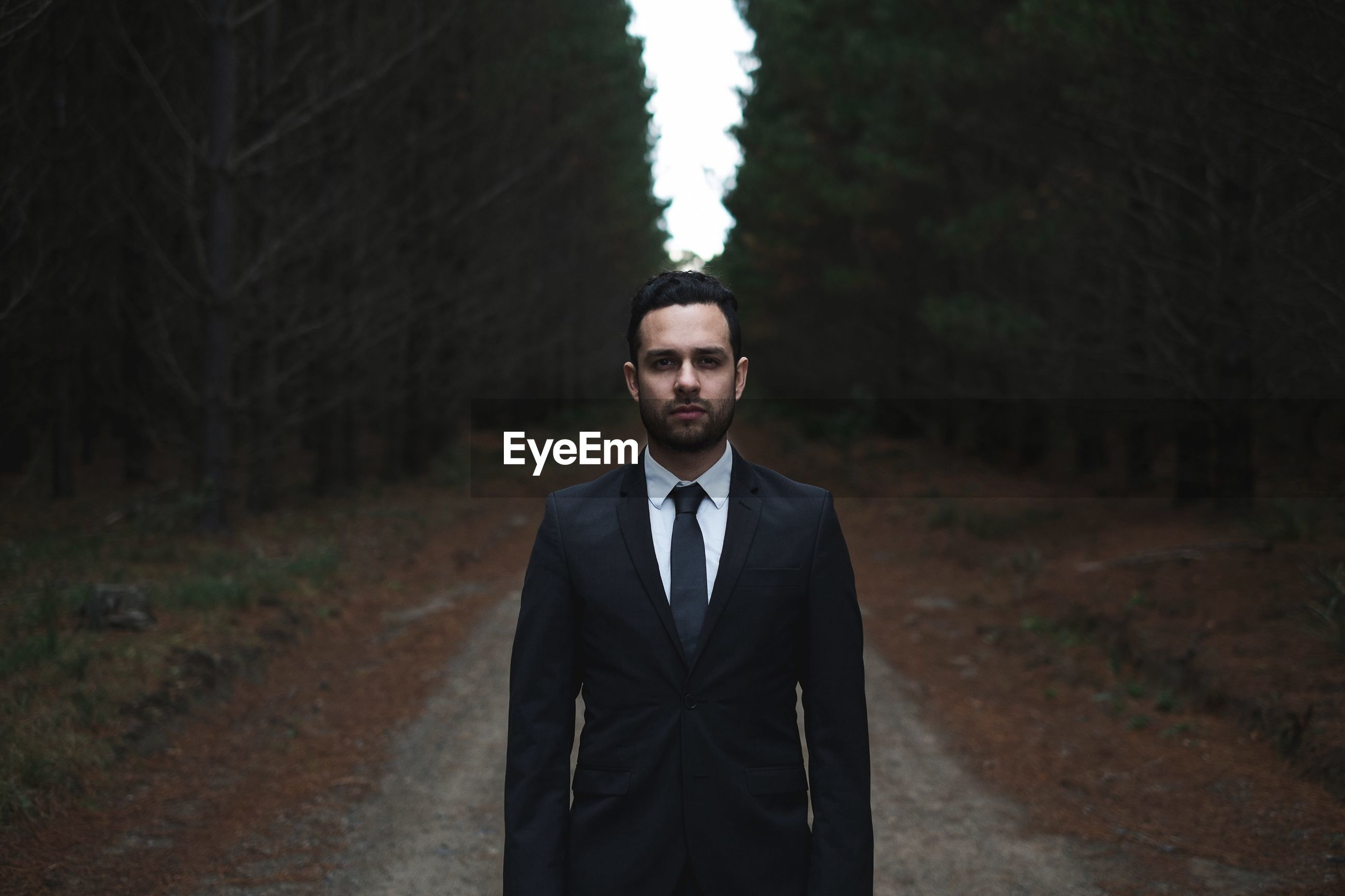 Man wearing suit in forest