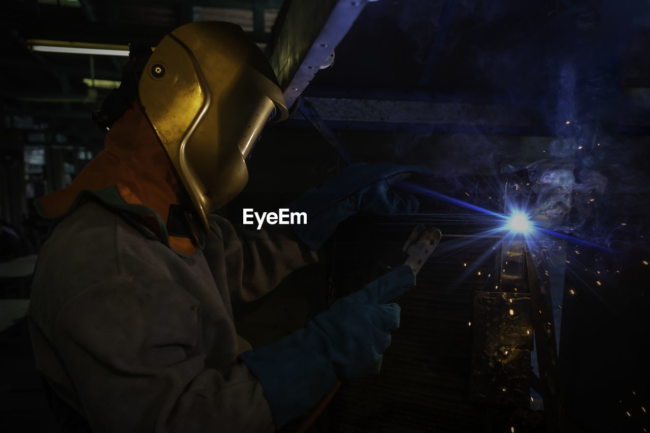 Man welding metal at workshop