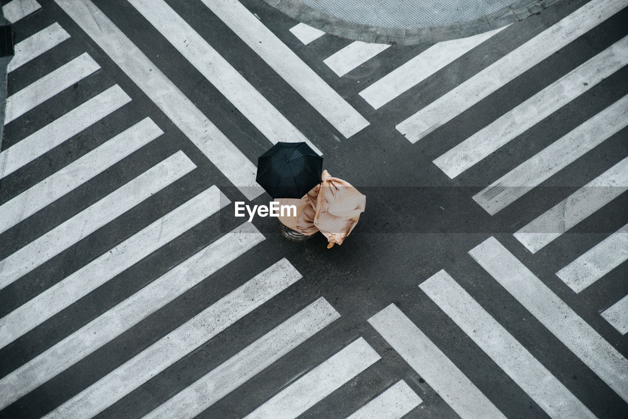 HIGH ANGLE VIEW OF MAN CROSSING ON ROAD