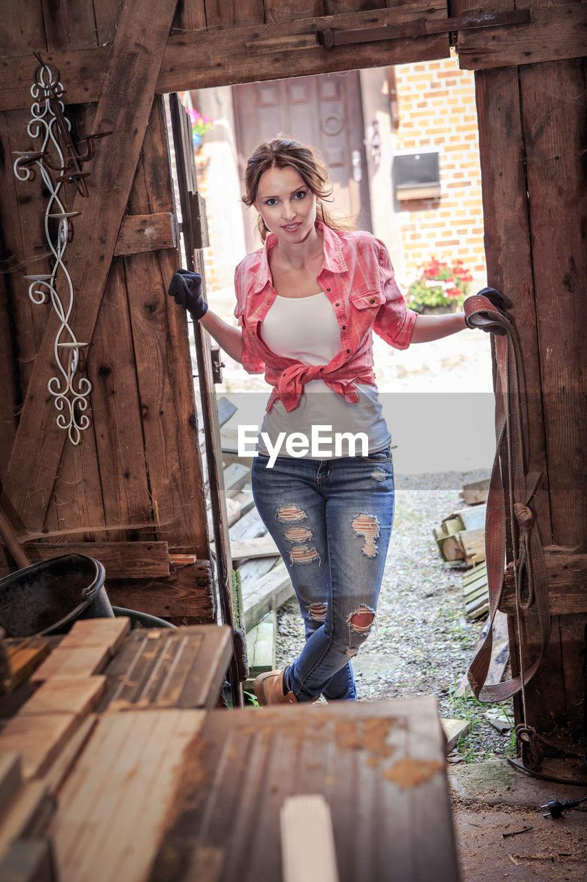 Portrait of mid adult woman standing at doorway