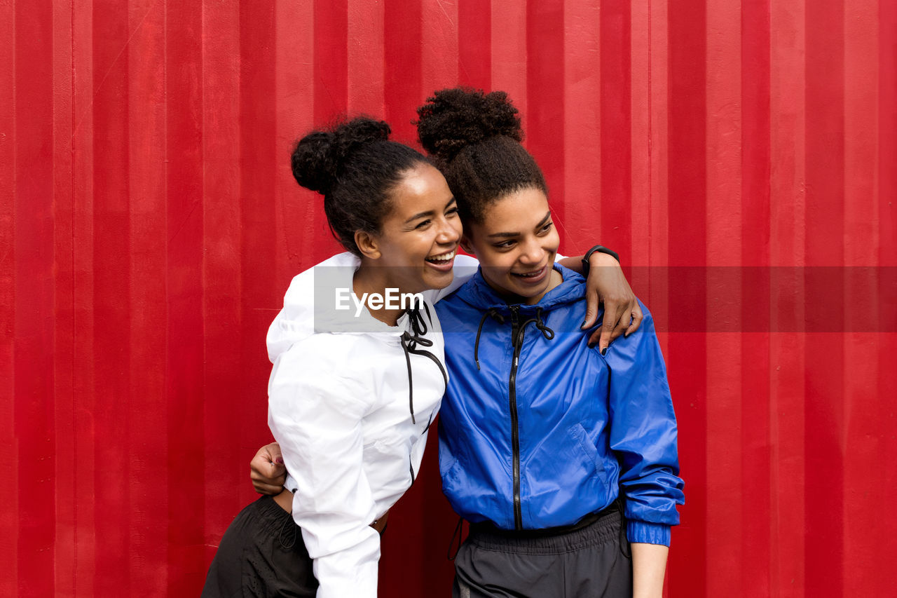 Cheerful Young Women Standing Against Red Cargo Container
