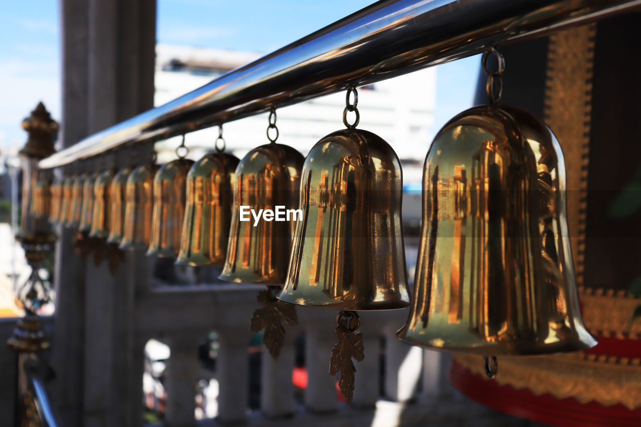 hanging, in a row, no people, metal, large group of objects, close-up, focus on foreground, side by side, bell, for sale, day, variation, choice, indoors, still life, architecture, selective focus, built structure, food and drink, retail display