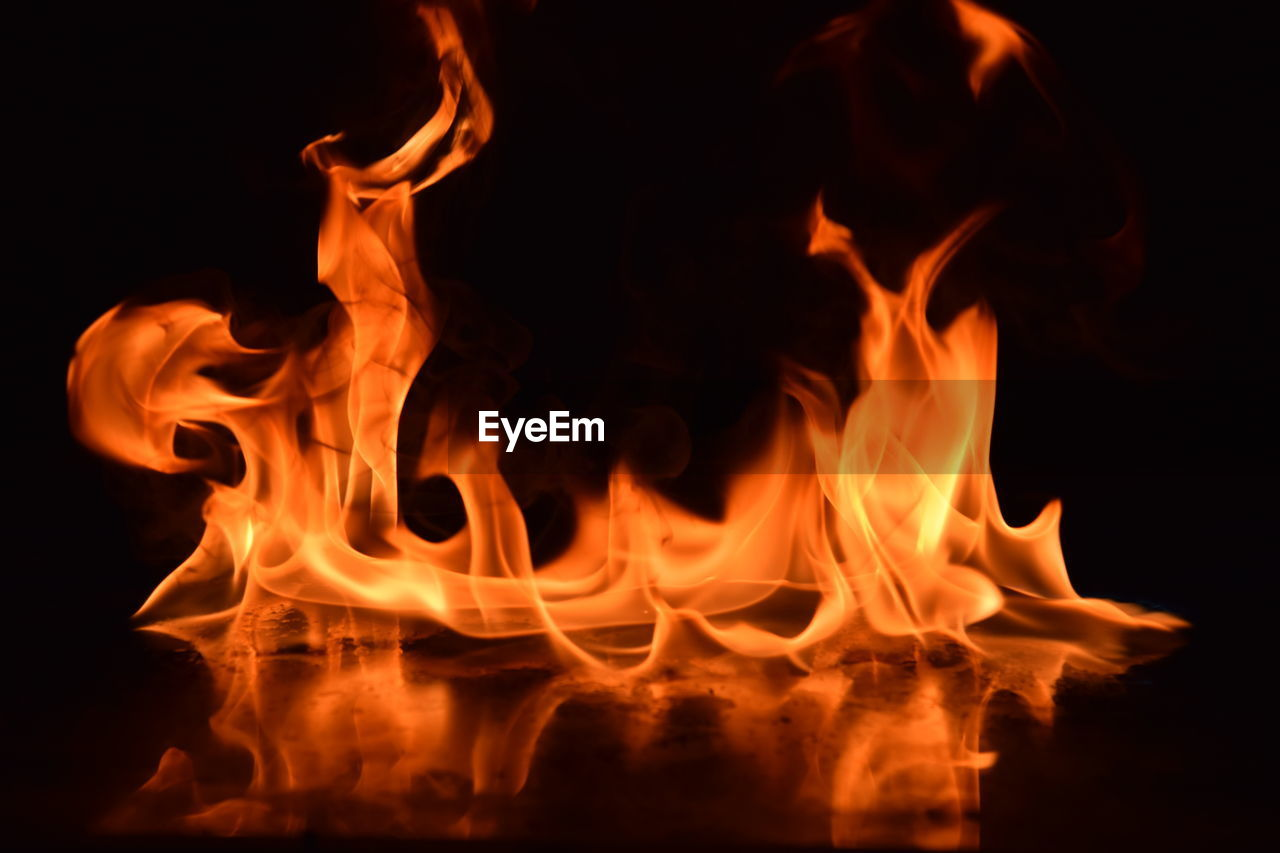 burning, fire, fire - natural phenomenon, heat - temperature, flame, motion, glowing, orange color, night, nature, no people, close-up, long exposure, blurred motion, black background, dark, outdoors, illuminated, environment, sign, bonfire