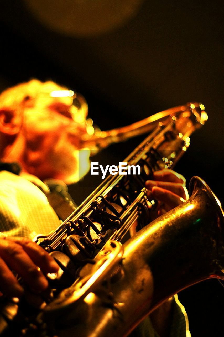 music, musical instrument, musician, playing, performance, arts culture and entertainment, saxophone, human hand, real people, event, rock music, skill, nightlife, wind instrument, performing arts event, one person, jazz music, close-up, night, guitar, outdoors, people