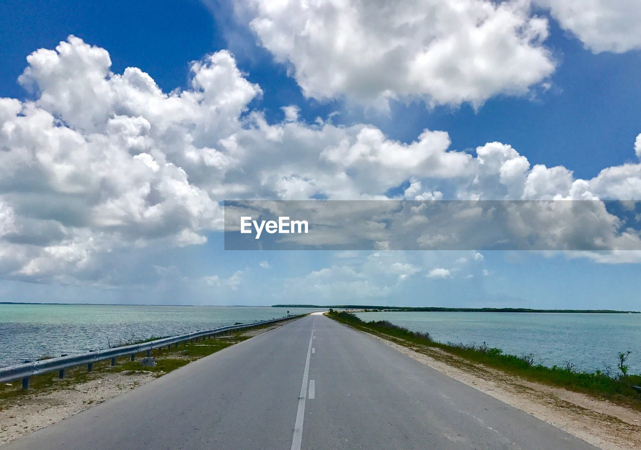 sky, cloud - sky, road, direction, the way forward, transportation, water, diminishing perspective, day, nature, horizon, vanishing point, sea, road marking, marking, beauty in nature, no people, scenics - nature, symbol, outdoors, horizon over water, long, dividing line