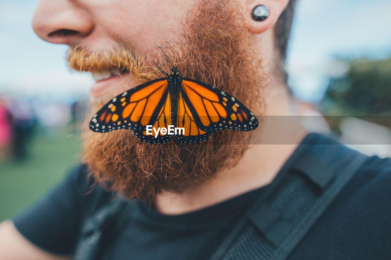 Midsection Of Man With Butterfly On Beard