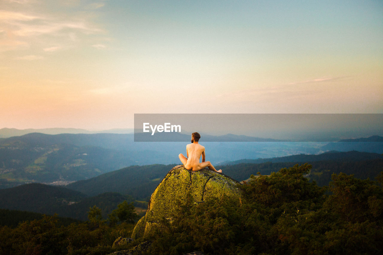 Rear view of naked man sitting on rock against mountains and sky