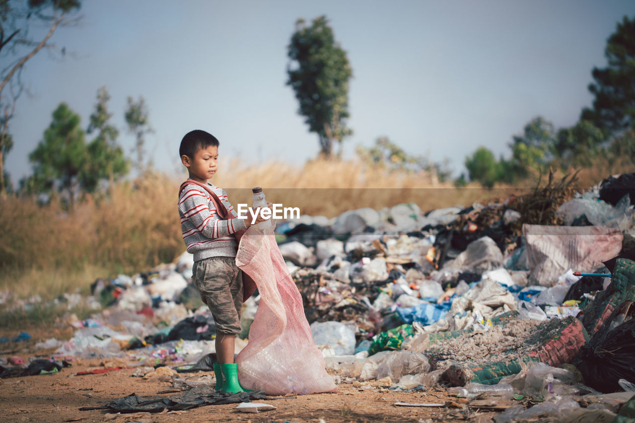 Full length of boy standing by garbage against sky