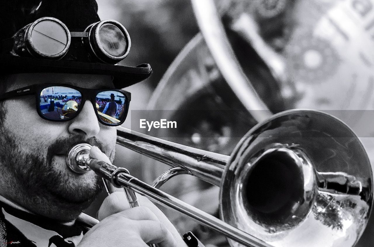 sunglasses, music, musical instrument, men, musician, real people, reflection, arts culture and entertainment, one person, eyeglasses, playing, wind instrument, outdoors, close-up, day, classical music, adult, people