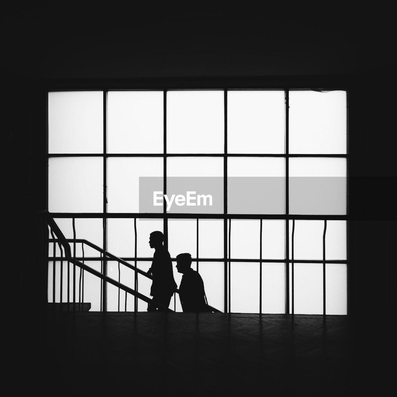 Silhouette People Standing In Window