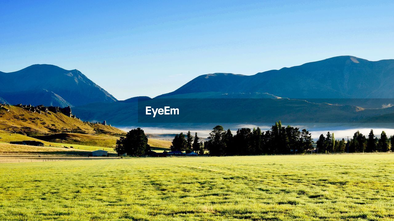SCENIC VIEW OF FIELD AGAINST MOUNTAINS