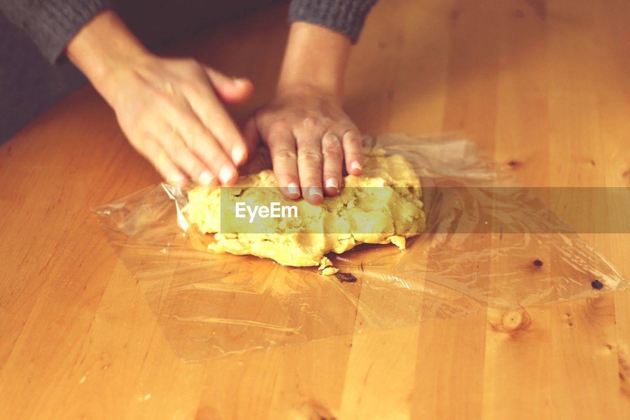 High Angle View Of Cropped Woman Hand Kneading Dough On Table
