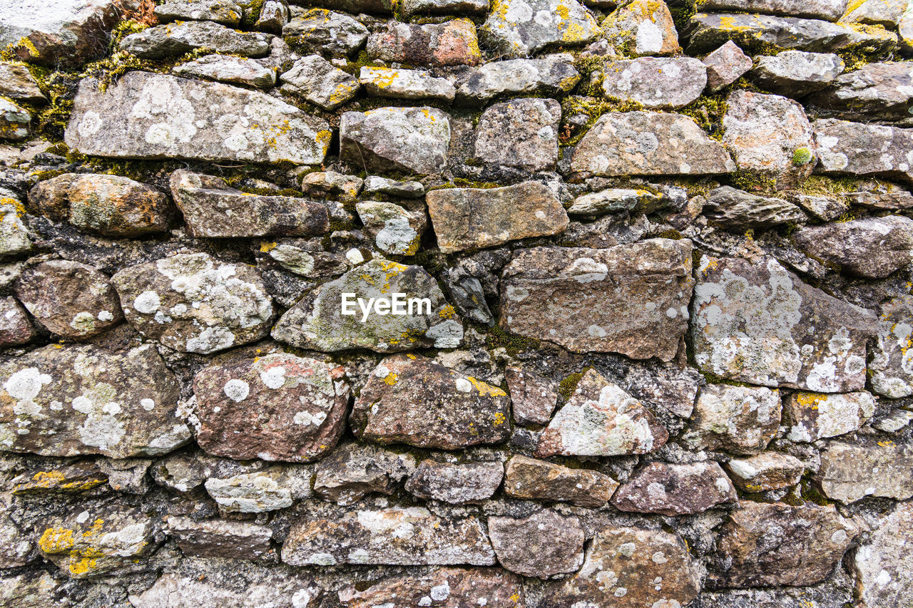FULL FRAME SHOT OF STONE WALL WITH STONES