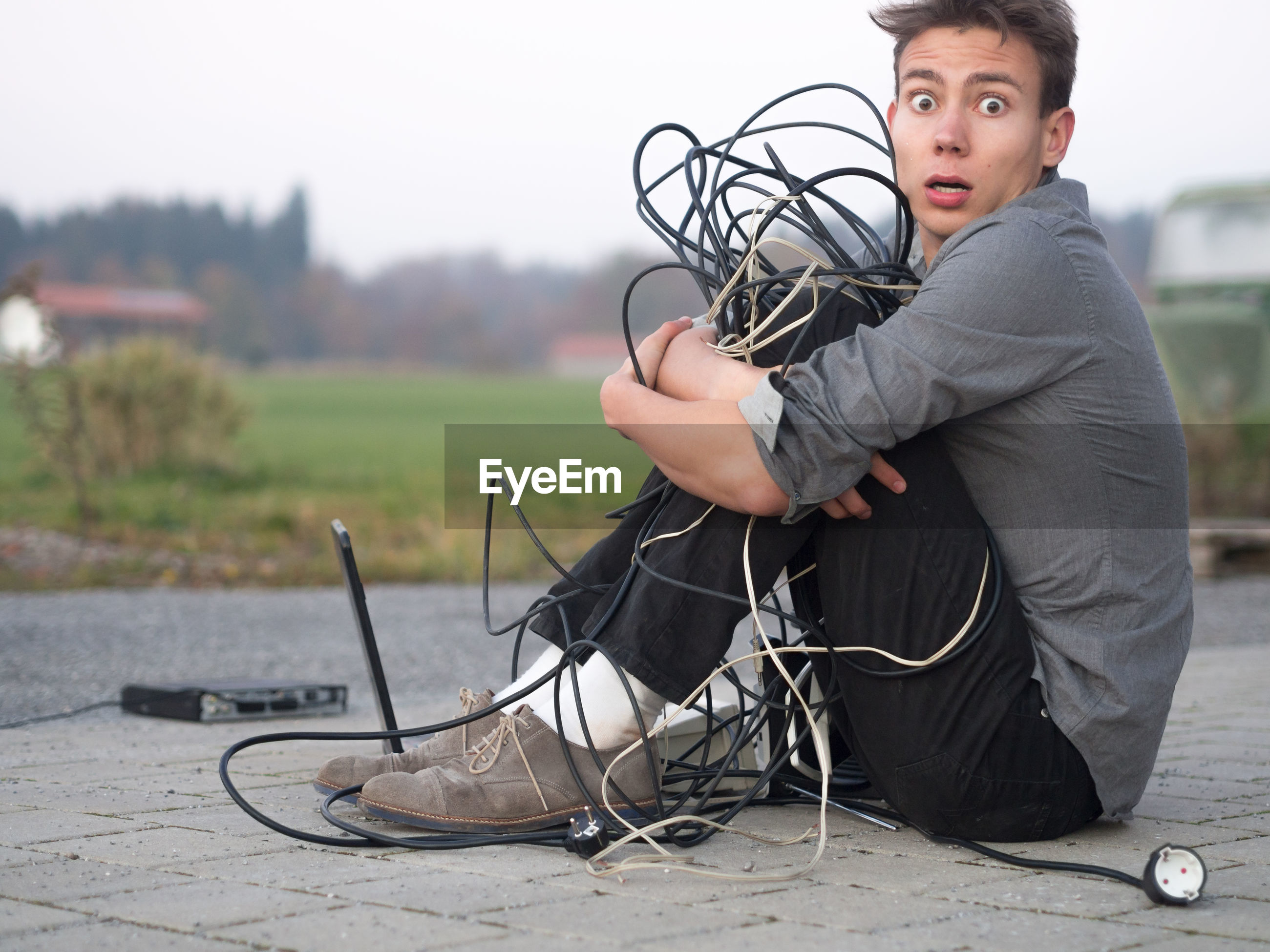Portrait of trapped man sitting in with tangled cables