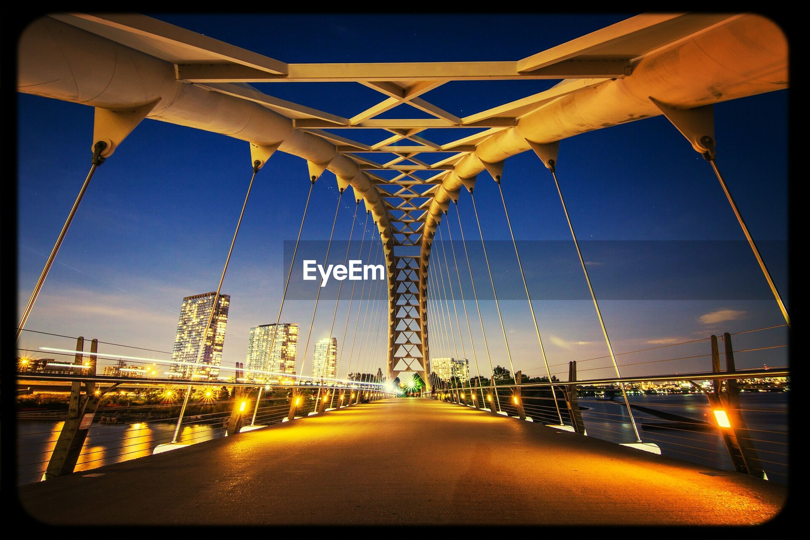 architecture, built structure, transfer print, connection, building exterior, illuminated, clear sky, transportation, bridge - man made structure, auto post production filter, city, the way forward, sky, diminishing perspective, engineering, bridge, outdoors, street light, no people, blue
