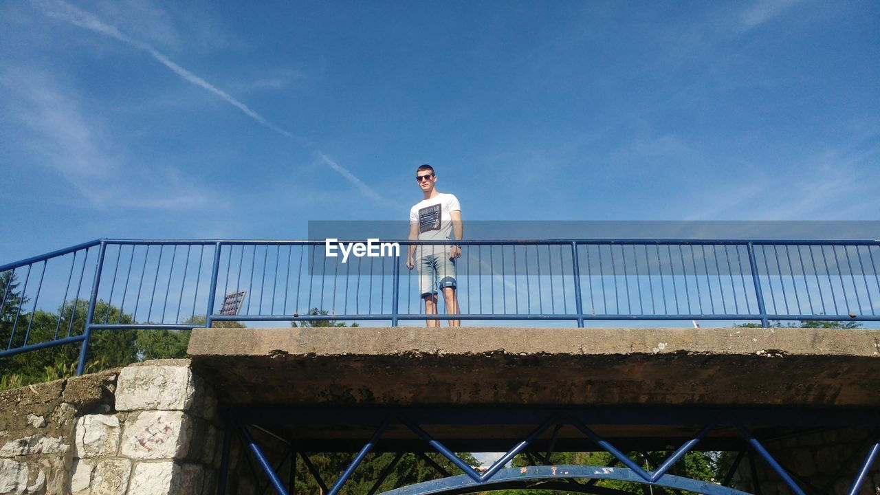 railing, full length, mid adult, bridge - man made structure, standing, mid adult men, outdoors, one person, sky, leisure activity, architecture, real people, casual clothing, day, lifestyles, low angle view, walking, built structure, blue, nature, young adult, people
