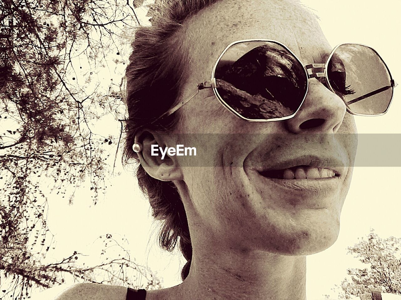 sunglasses, glasses, fashion, headshot, portrait, one person, close-up, smiling, real people, lifestyles, security, protection, day, tree, nature, young adult, leisure activity, mid adult, outdoors, human face