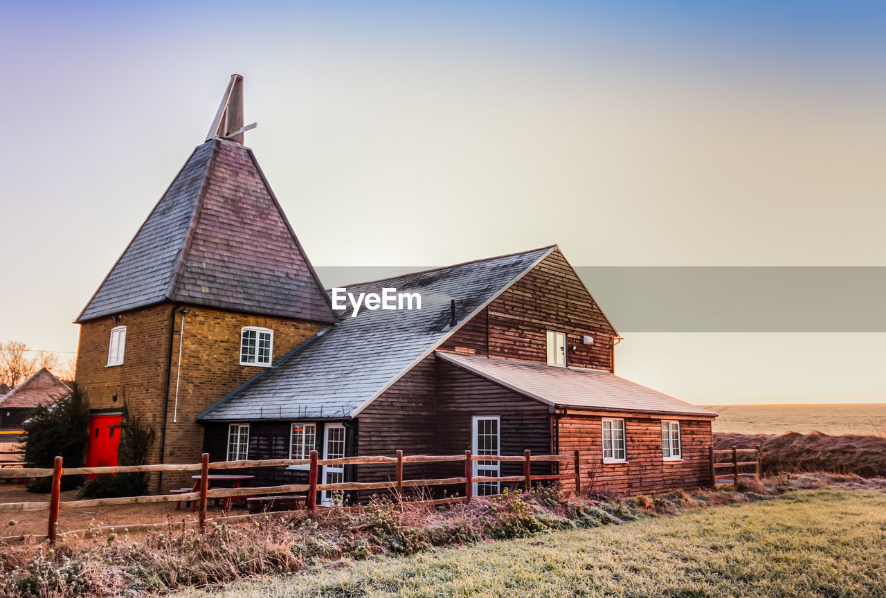 architecture, built structure, building exterior, sky, building, house, nature, grass, no people, clear sky, landscape, field, plant, rural scene, land, day, copy space, religion, wood - material