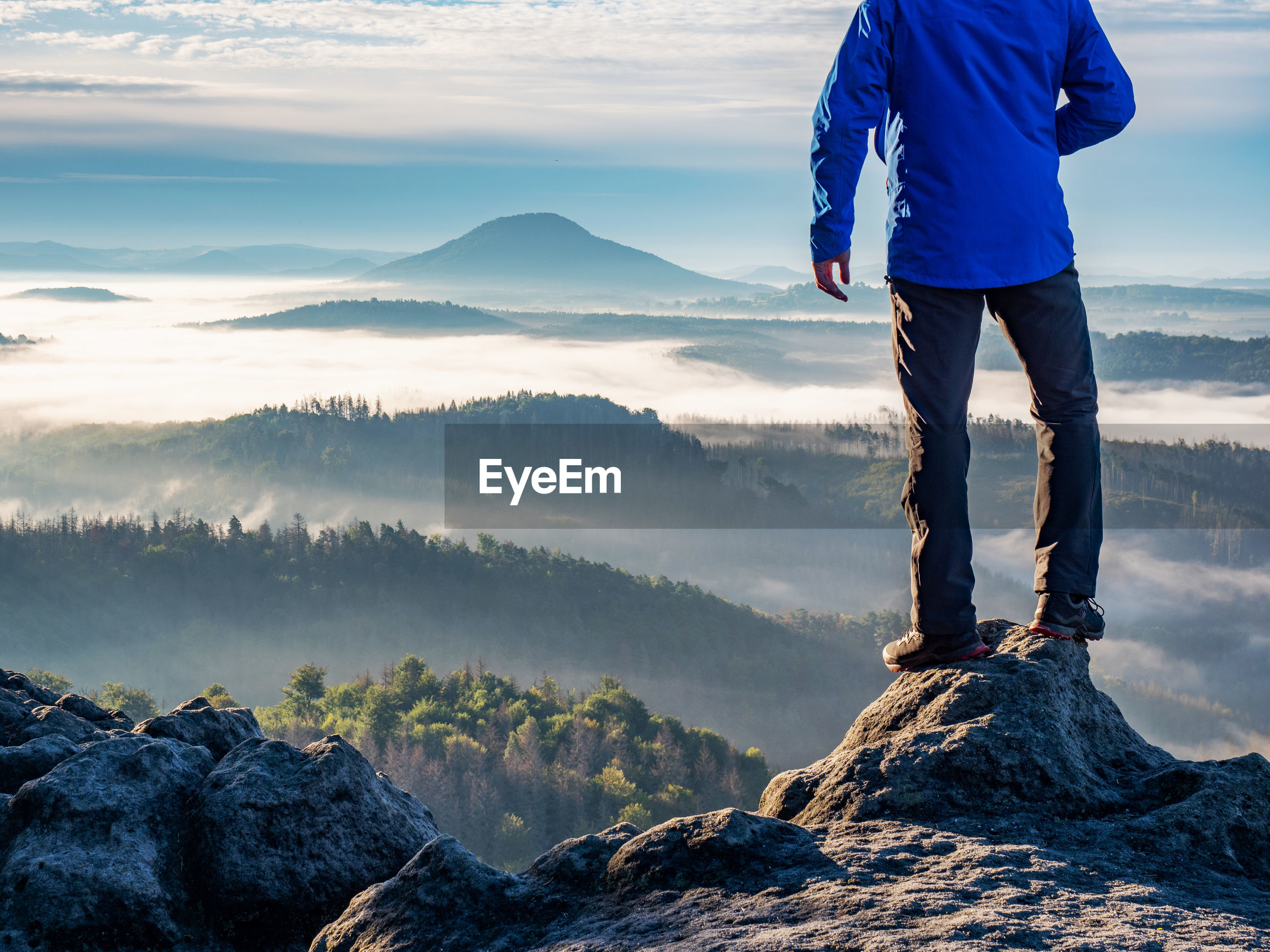 Man watch thick mist in valley from rocky view point in mountains. hiker climbed up alone