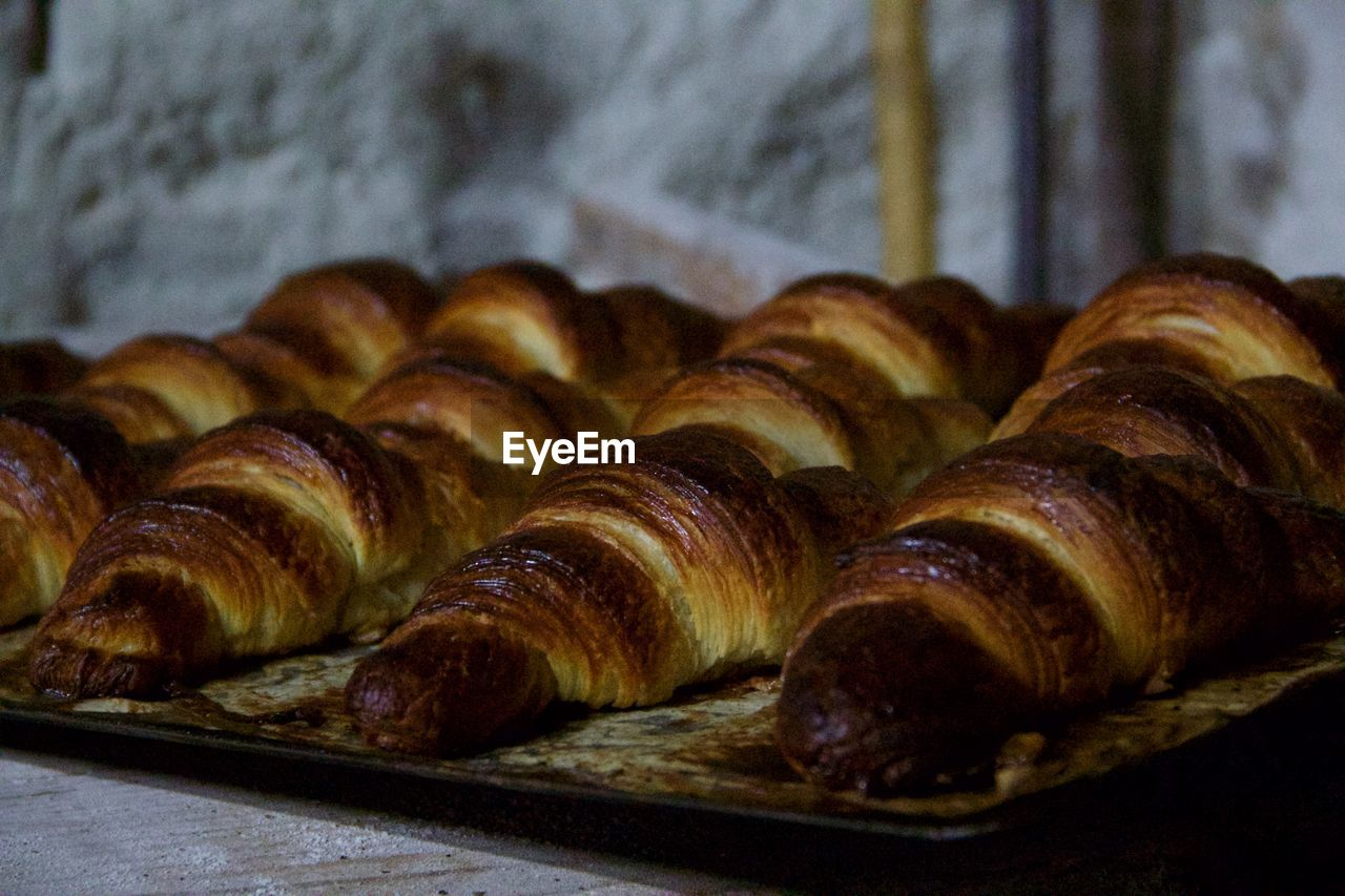 food and drink, food, baked, freshness, still life, no people, close-up, indoors, ready-to-eat, french food, croissant, bread, in a row, baked pastry item, focus on foreground, for sale, table, brown, indulgence, store, bun, tray, baking sheet, temptation, snack