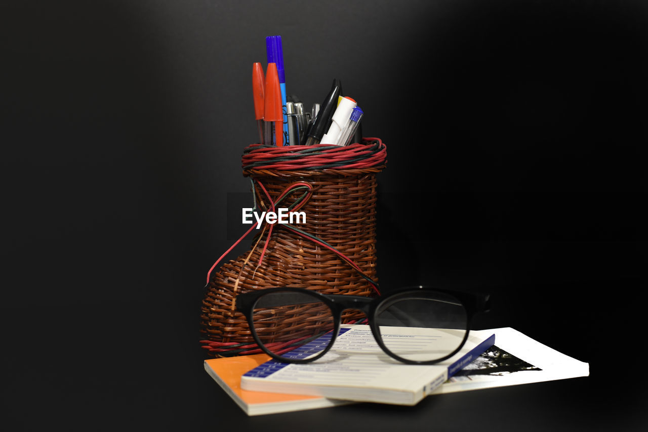 indoors, glasses, still life, copy space, desk organizer, publication, black background, book, no people, pencil, close-up, education, table, pen, studio shot, paper, container, eyeglasses, writing instrument, reflection, personal accessory