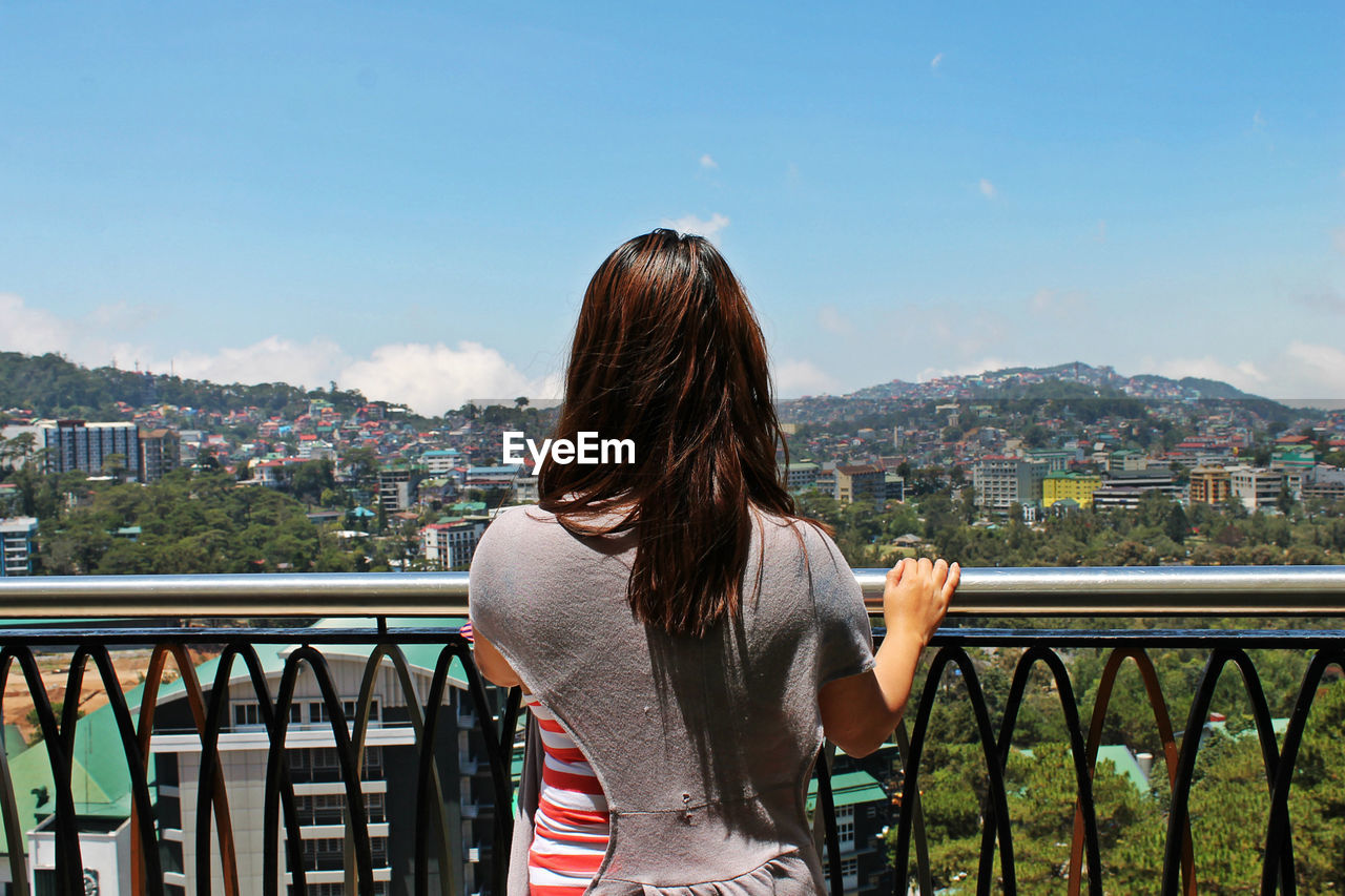 Rear view of woman looking at cityscape