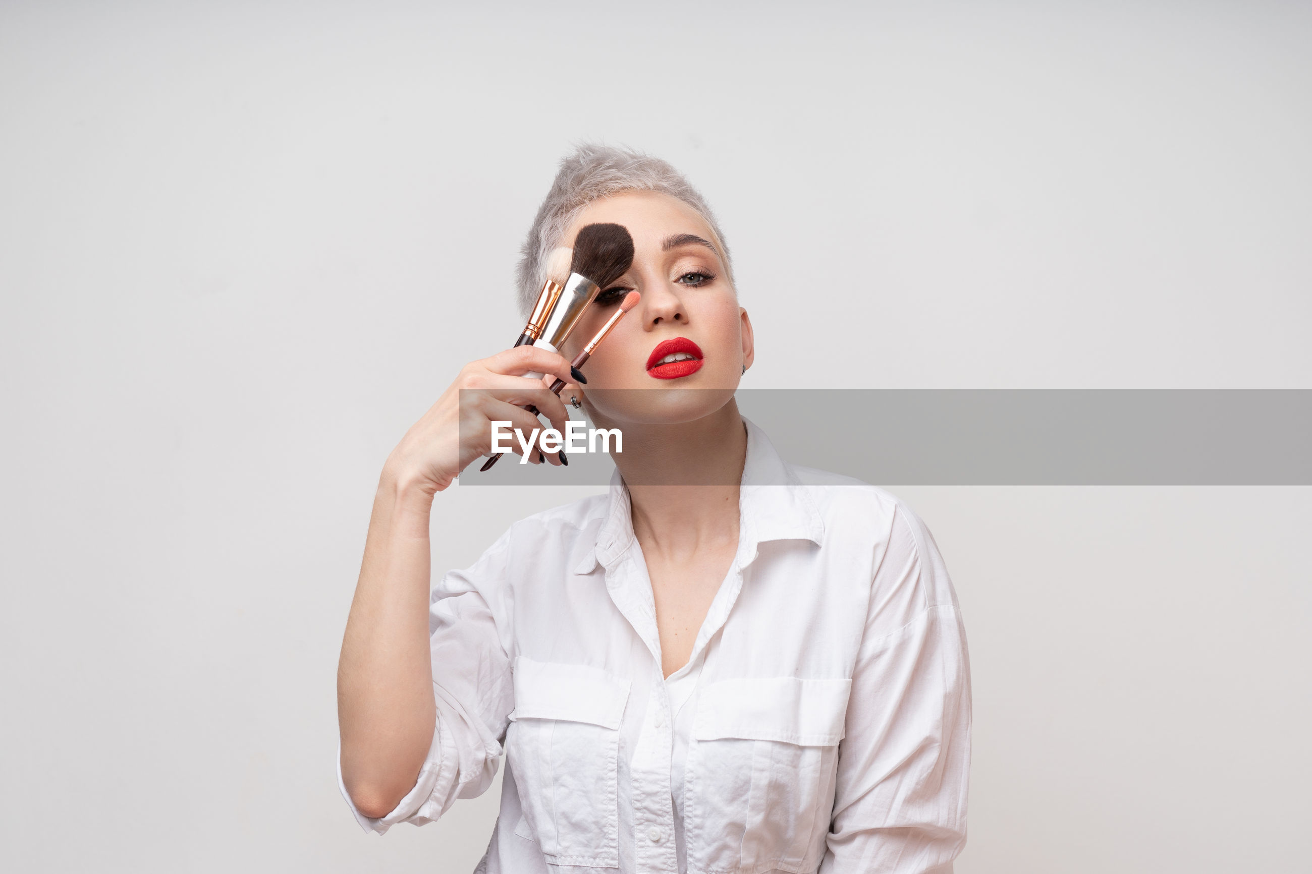Portrait of young woman holding beauty products against white background