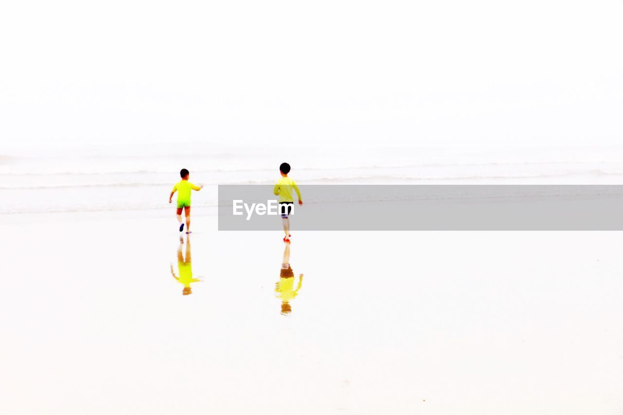 full length, real people, men, two people, sea, rear view, walking, beach, togetherness, sand, scenics, beauty in nature, young men, shirtless, lifestyles, nature, water, white background, day, outdoors, bonding, ankle deep in water, young adult, clear sky, sky, adult, people