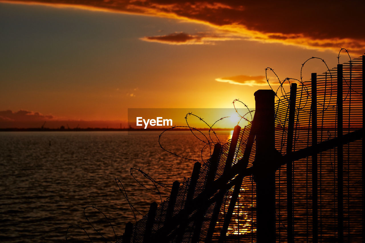 sunset, sky, orange color, water, beauty in nature, scenics - nature, cloud - sky, nature, sea, silhouette, architecture, no people, fence, barrier, built structure, railing, outdoors, tranquility, boundary
