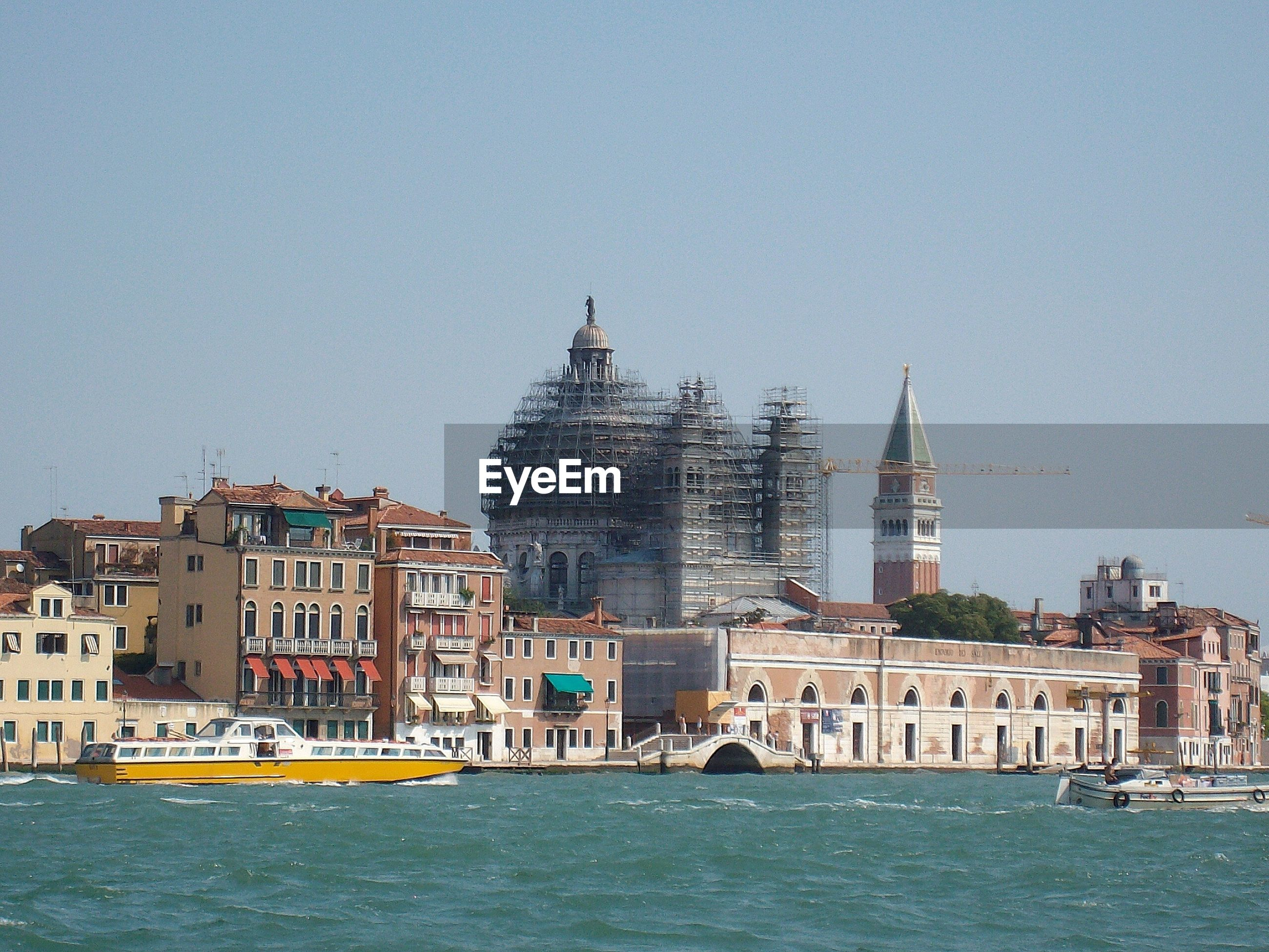 San marco campanile and incomplete santa maria della salute by canal against clear sky