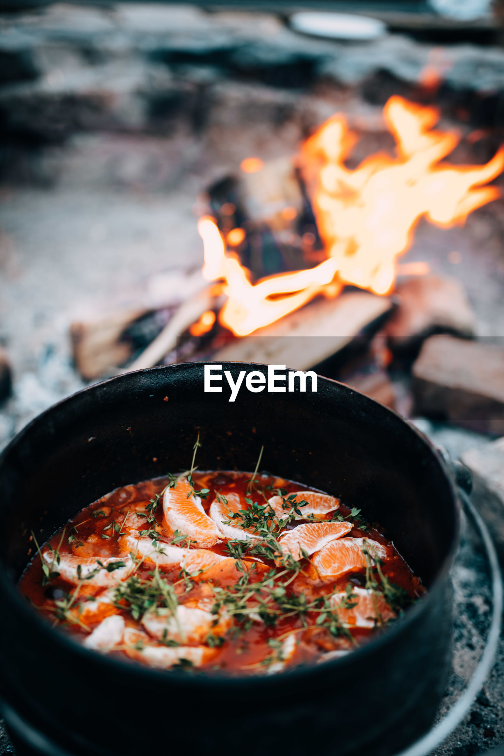 High angle view of food in container by campfire
