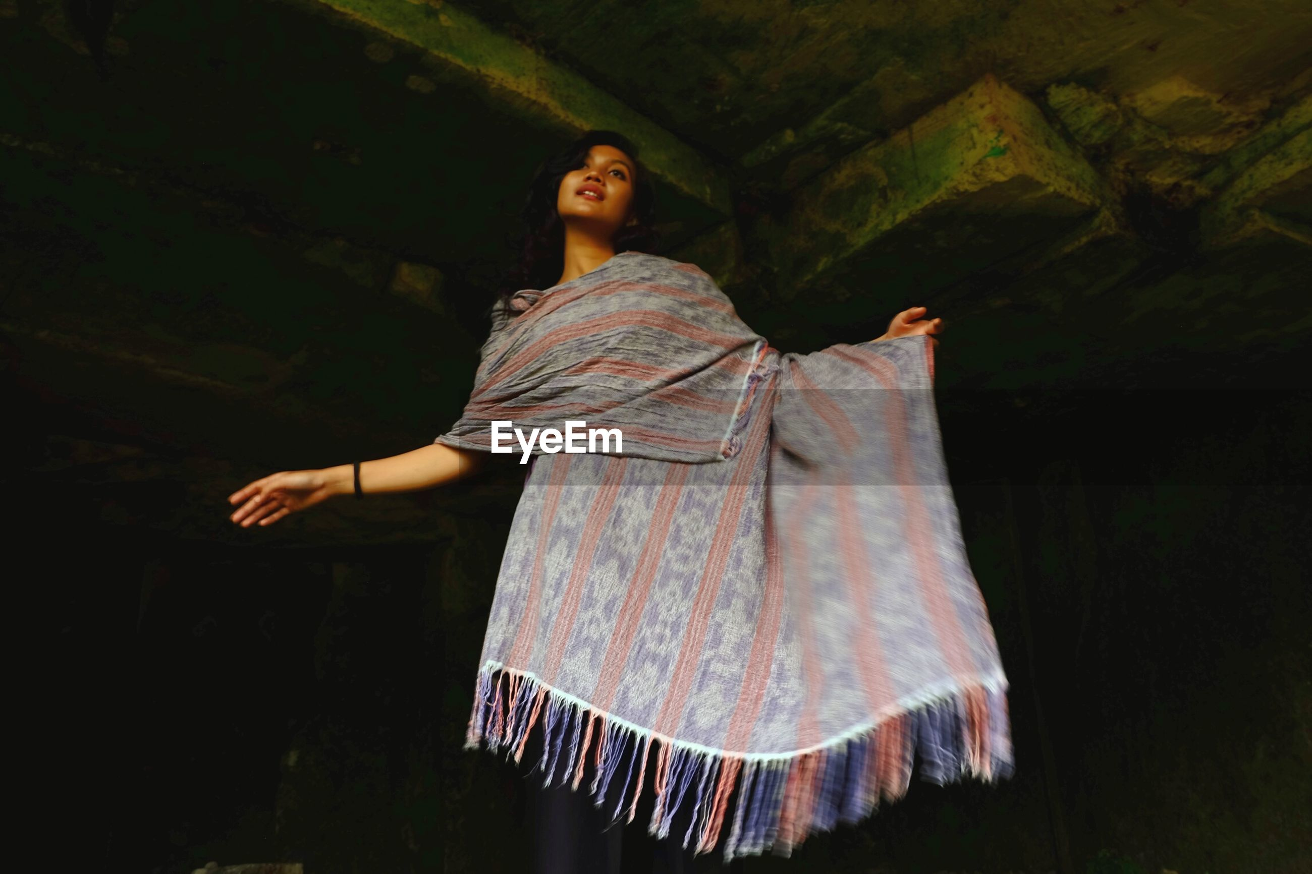 Low angle view of woman wrapped in dupatta while standing in darkroom