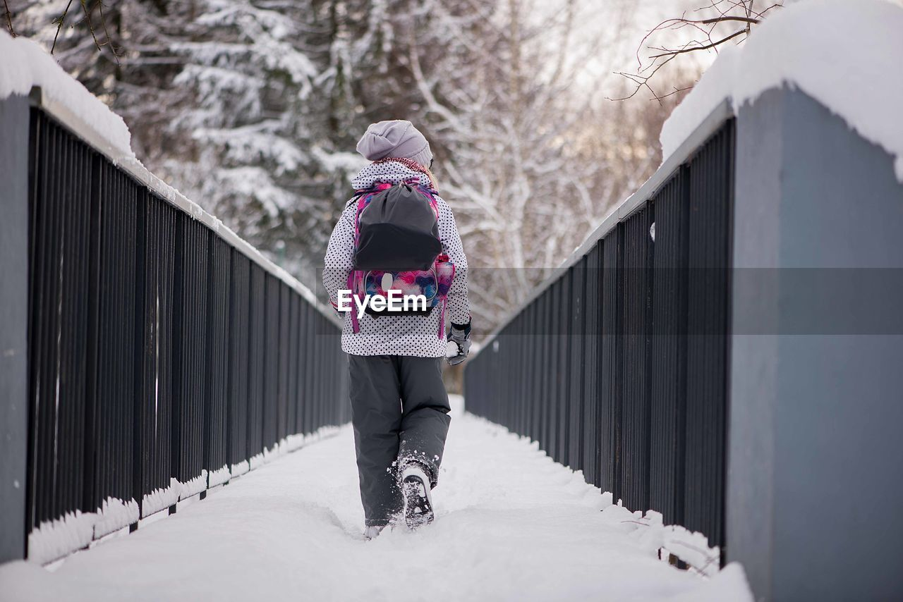 winter, cold temperature, snow, warm clothing, clothing, real people, rear view, one person, lifestyles, full length, women, standing, built structure, day, leisure activity, tree, covering, architecture, outdoors, extreme weather, winter coat