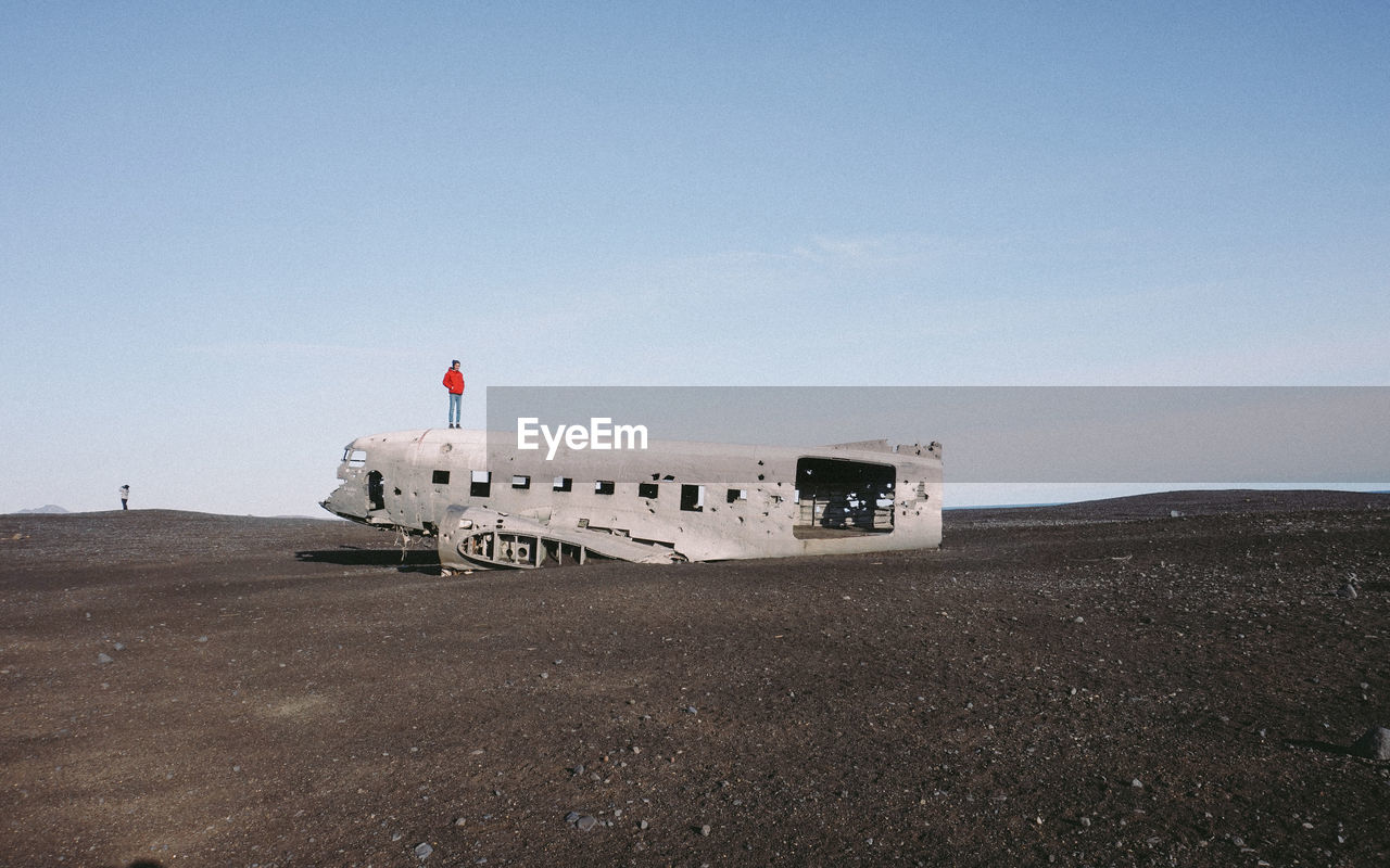 Person Standing On Crashed Airplane On Black Sand Against Sky
