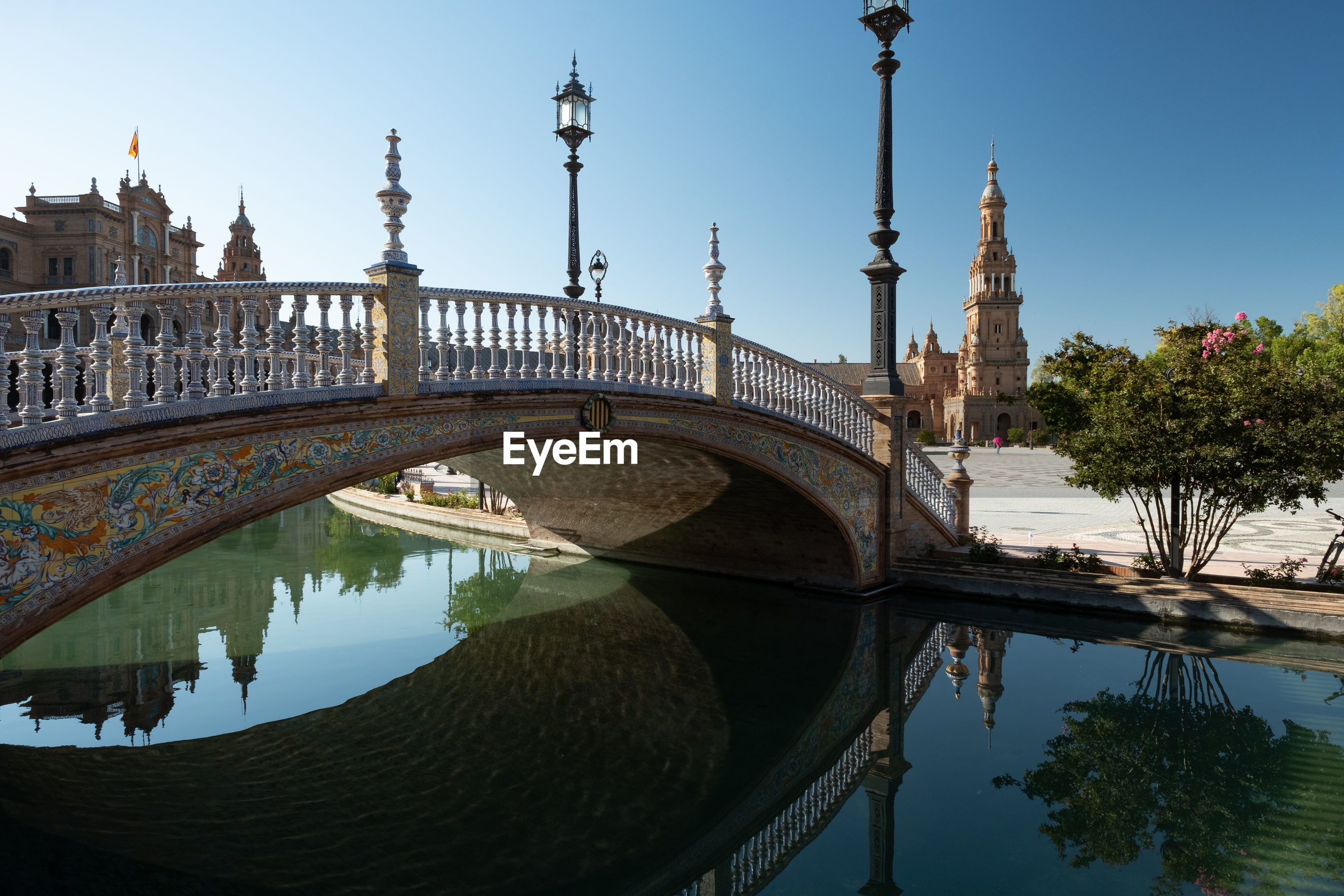 Bridge over water in city against clear sky